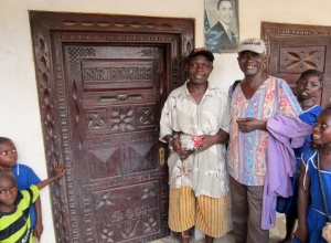 Mr. Bendu, left, of Moyeamoh village, proudly wears his Obama hat in front the Obama picture on his front porch. (He's holding the chicken I've been presented with.)