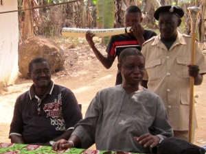 Paramount Chief Caulker in village meeting with his official staff bearer & horn blower.