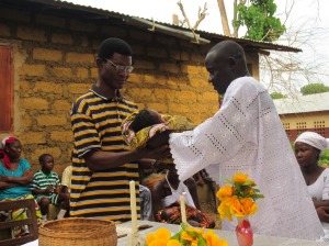 Father hands newborn baby to the pastor for blessing at Naming Ceremony.