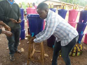 CCET Exec. Director Rosaline Kaimbay demonstrates the hand washing station.