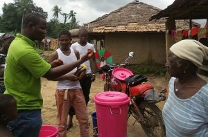 Alpha Mansaray delivers hand washing stations and Ebola prevention message to villagers.