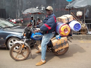 Rev Williams load his motorcycle to carry supplies to Shenge